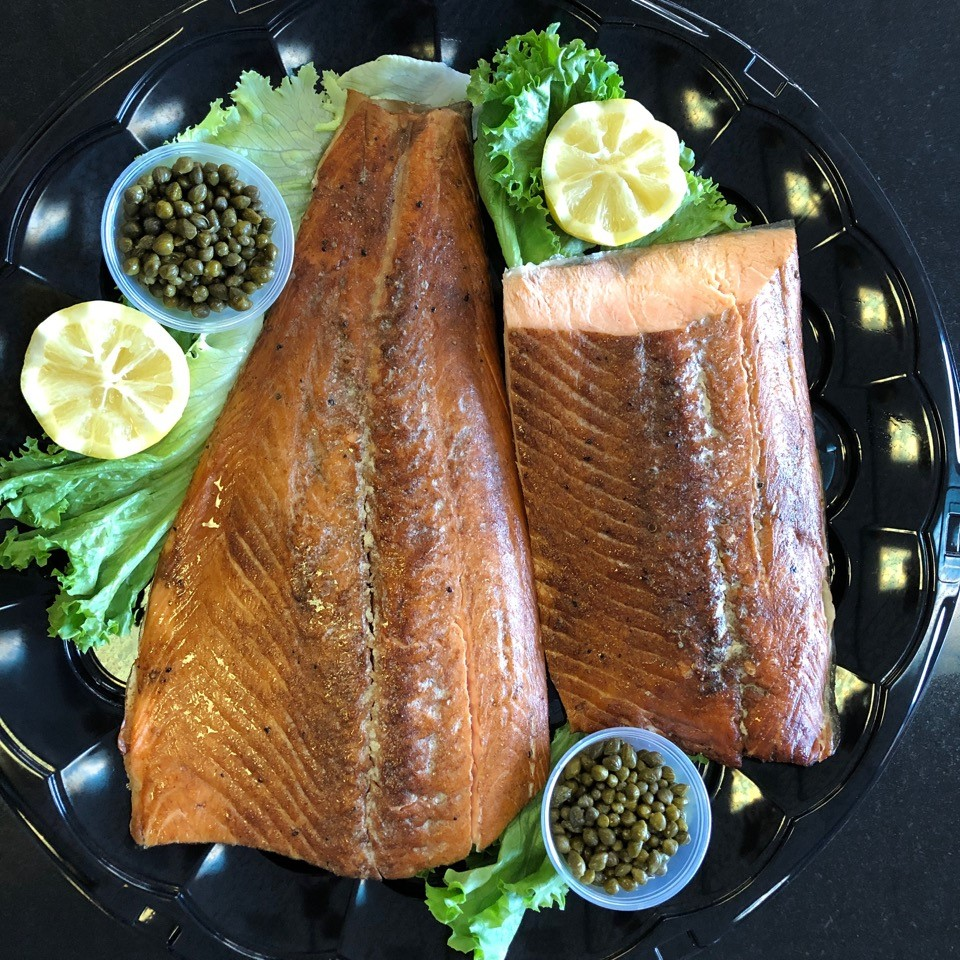 large grilled salmon on a tray with lemon and capers