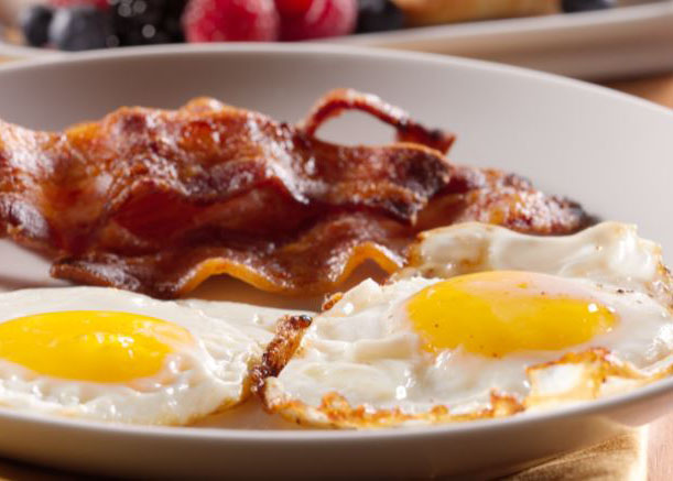 2 sunny side up eggs with a side of bacon