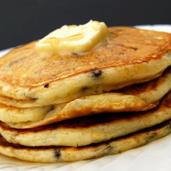 A stack of blueberry pancakes topped with butter