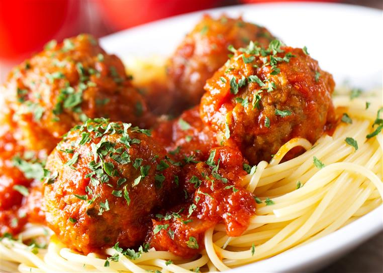 Spaghetti topped with meatballs and sauce