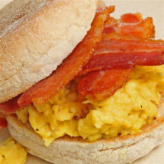 An egg sandwich on an English muffin, topped with bacon