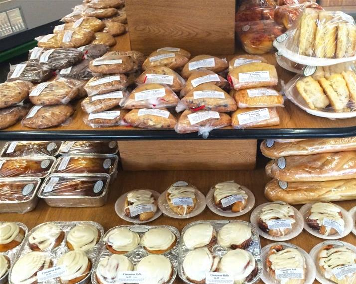 assorted baked goods and pastries on display inside the market