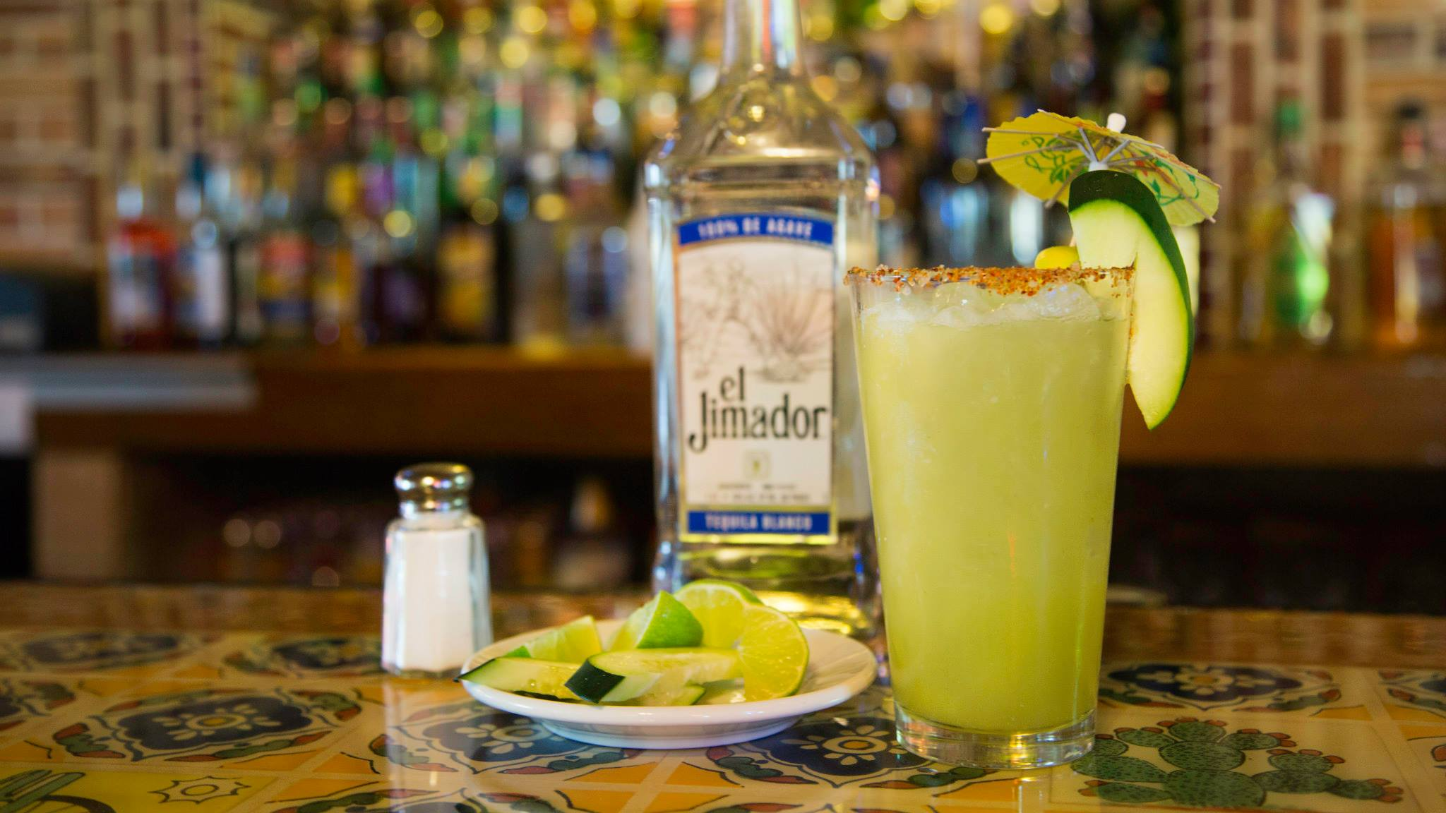margarita in a tall glass with limes and a bottle of tequila