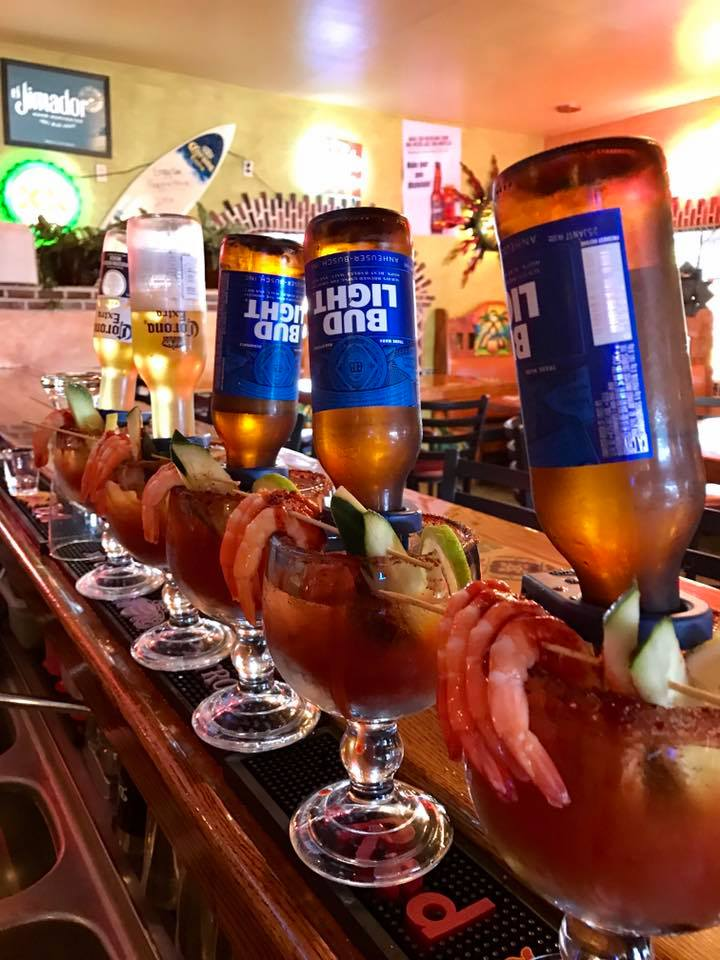 five michelada cocktails lined up on the bar