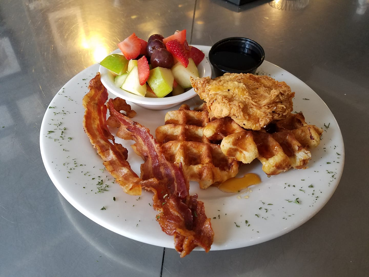 chicken and waffles with bacon strips and a side salad with a cup of syrup