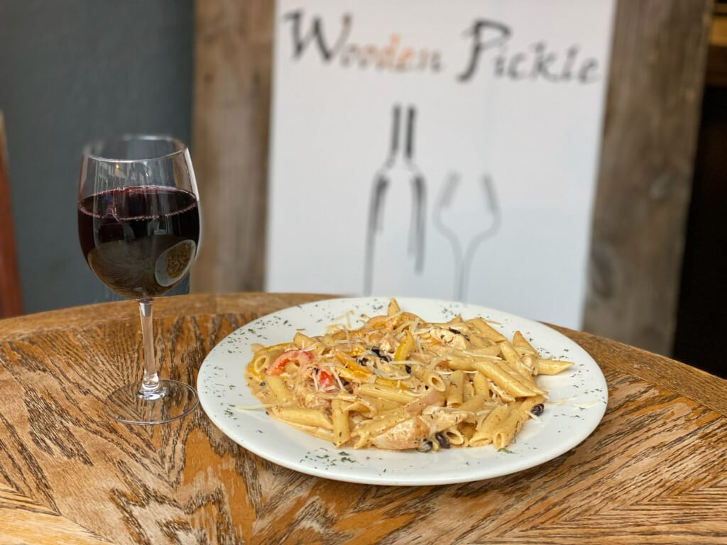 creamy cajun pasta with chicken, tomatoes and shredded cheese with a glass of red wine
