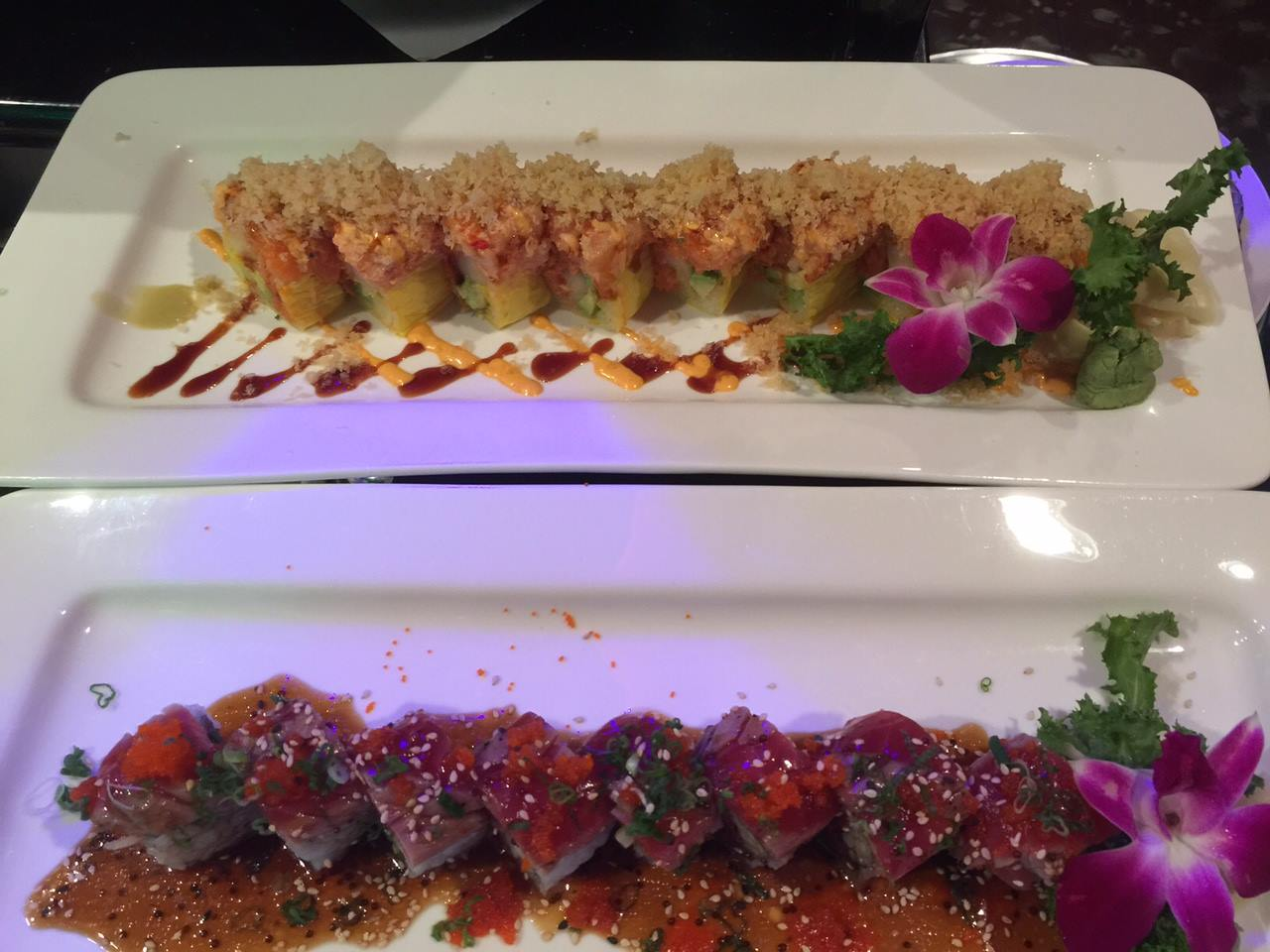 two plates of sushi rolls
