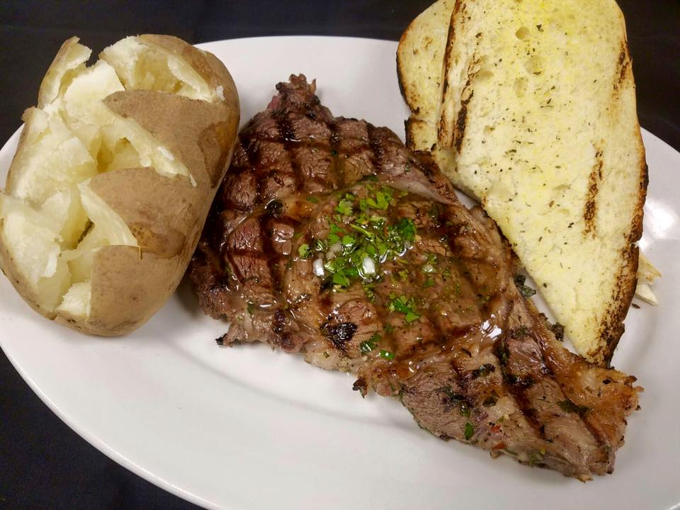 grilled ribeye with a slice of garlic bread and a baked potato on the side.