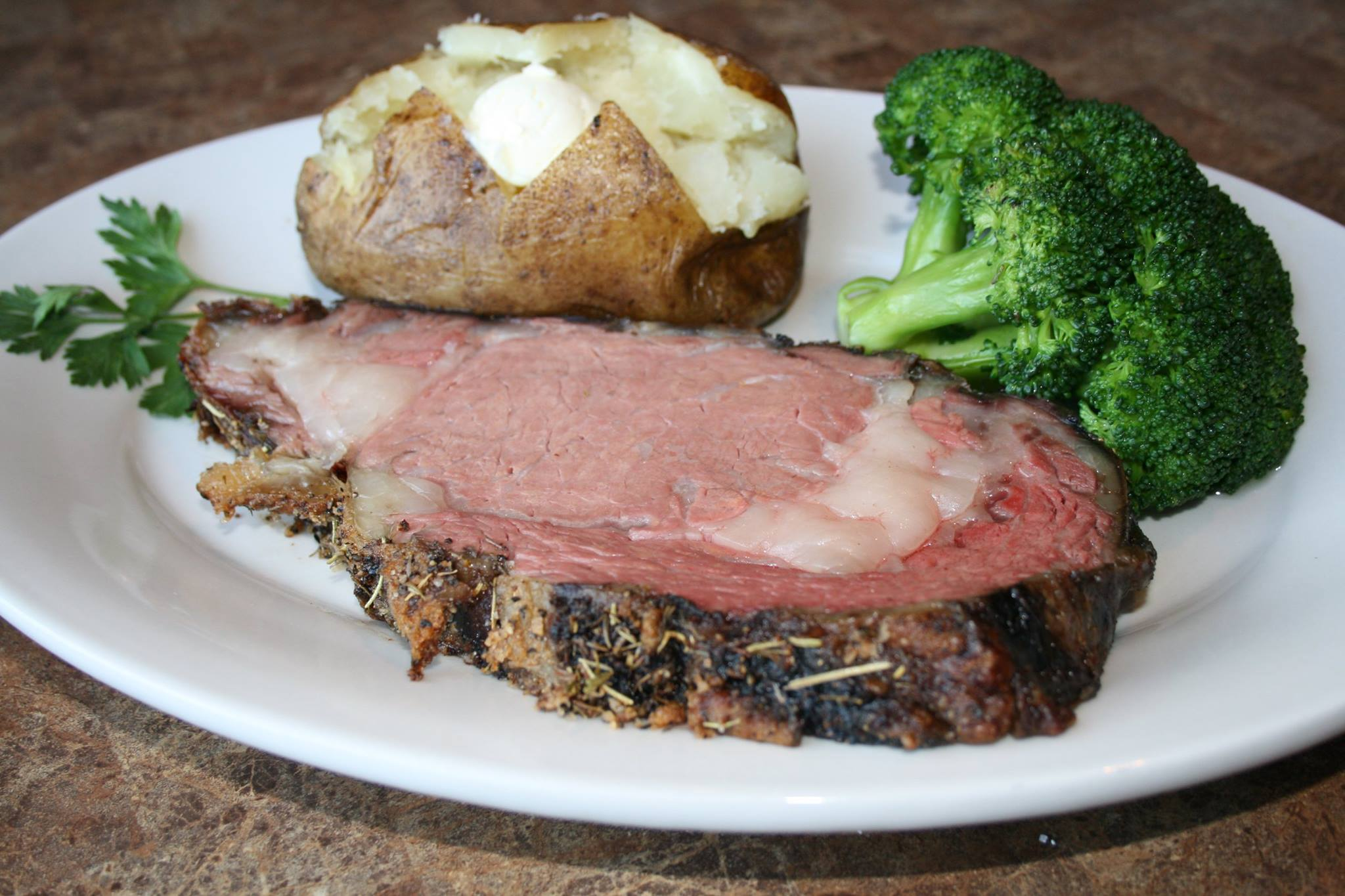 prime rib cooked medium rare with broccoli and a baked potato on the side.