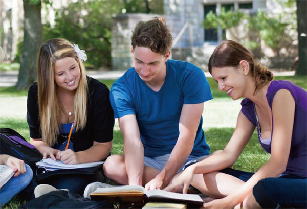 students outside reading a book on a college campus