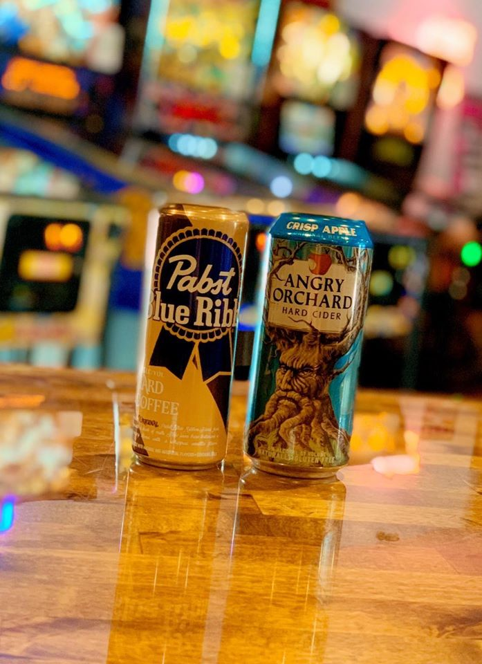 can of pabst blue ribbon and can of angry orchard hard cider on the the bar.