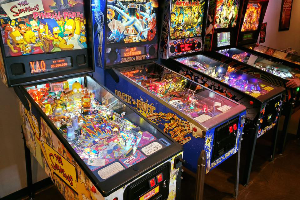 different arcade games lined up against the wall.