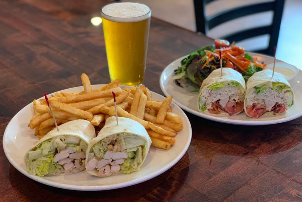 Chicken Caesar Wrap and BLT Wrap on a table with a pint glass of light beer