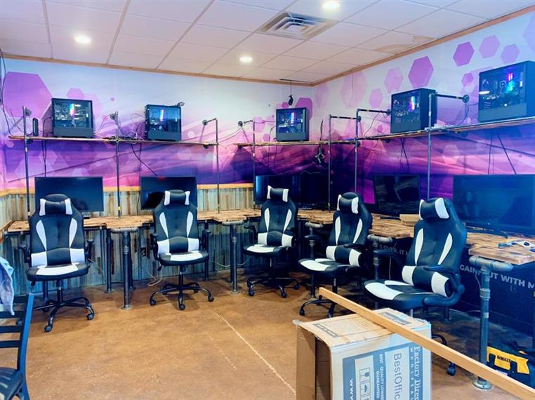 Pixel paradise room that has desks aligned the walls with computers and chairs for gaming.