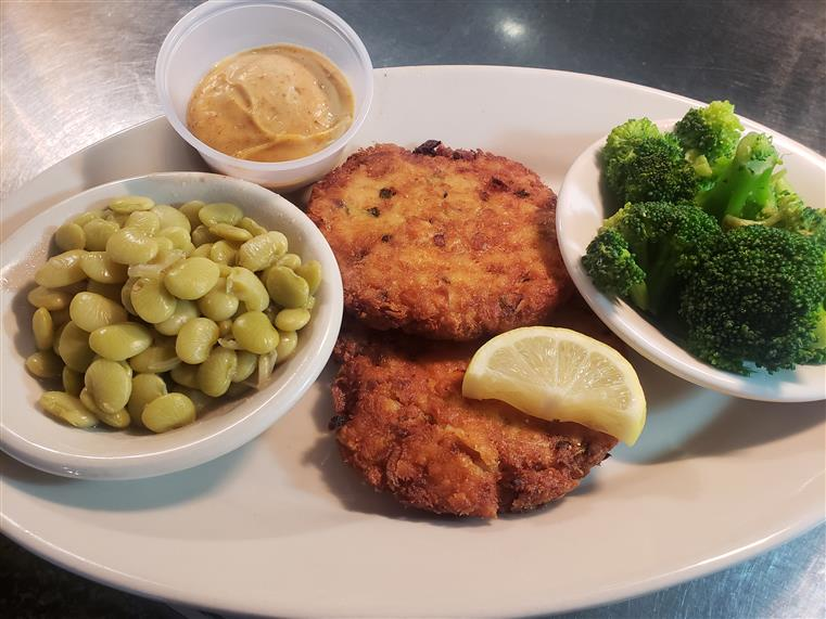 crab cakes on a plate with beans, steamed broccoli, and dipping sauce