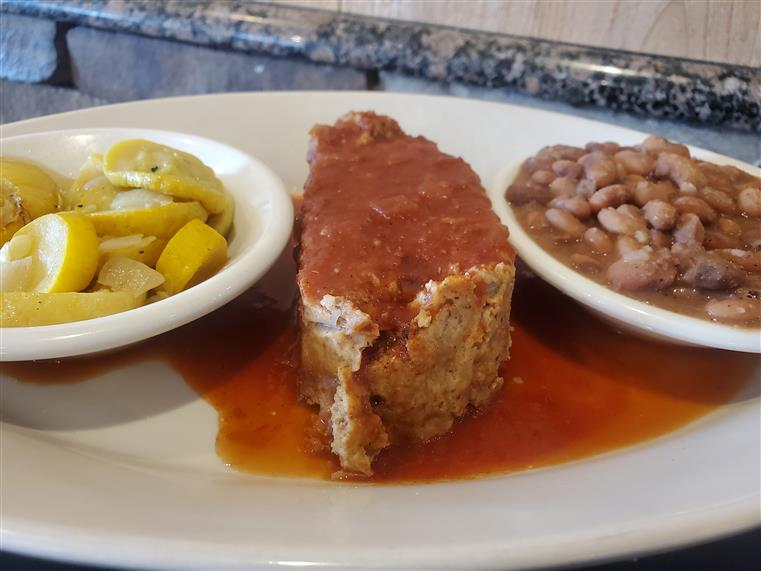 piece of meatloaf covered in tomato sauce, with sides of squash and beans