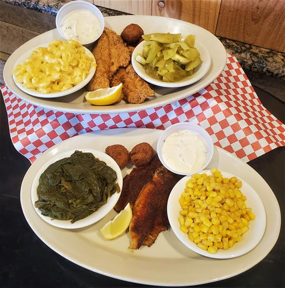 two plates of fried catfish with sides of corn, greens, mac and cheese, and tartar sauce
