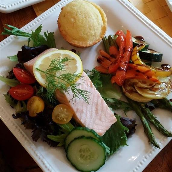 baked salmon on top of a fresh green salad served with roasted seasonal vegetables, a cornmuffin, and garnished with fresh lemon and dill