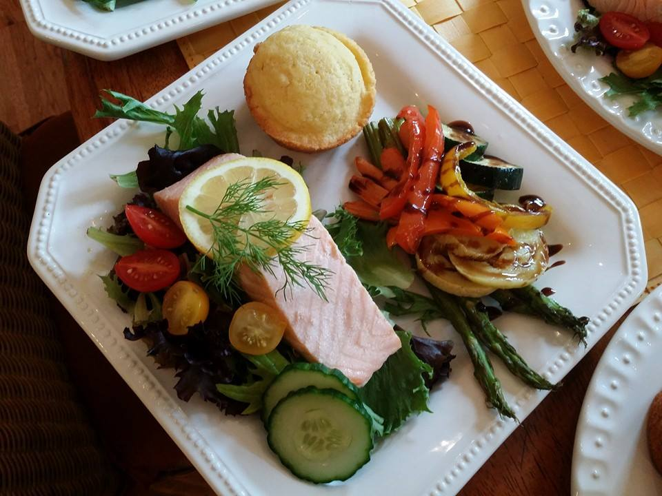 fish plate including salmon over grilled vegetables, a corn muffin and more grilled vegetbale son the side