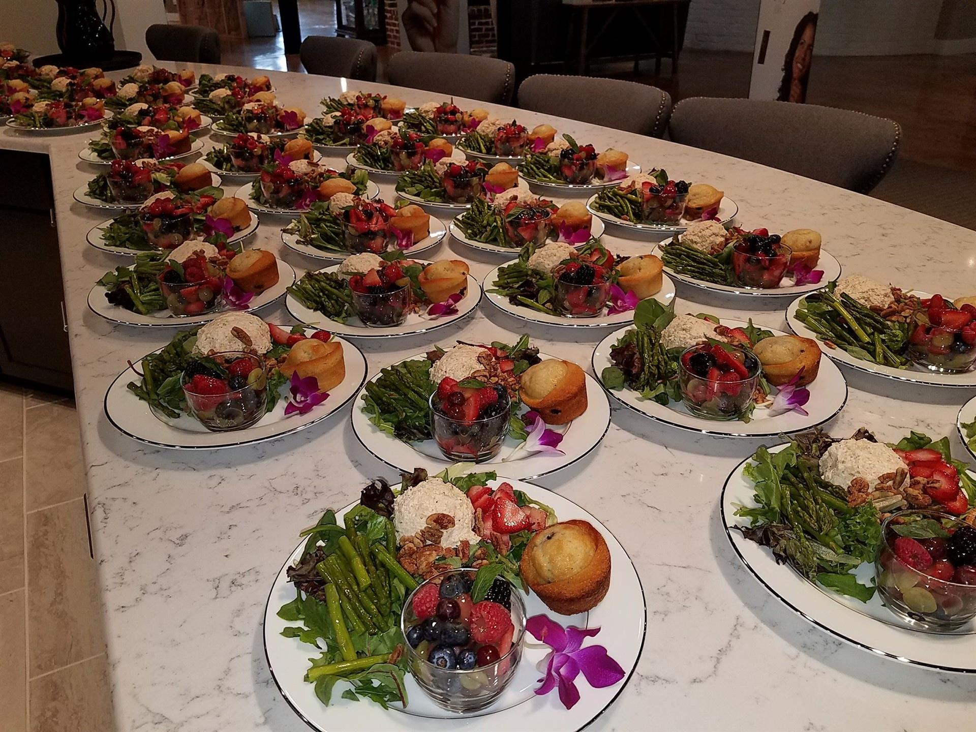 plates set with meals including grilled apsargus and mixed berry fruit cups