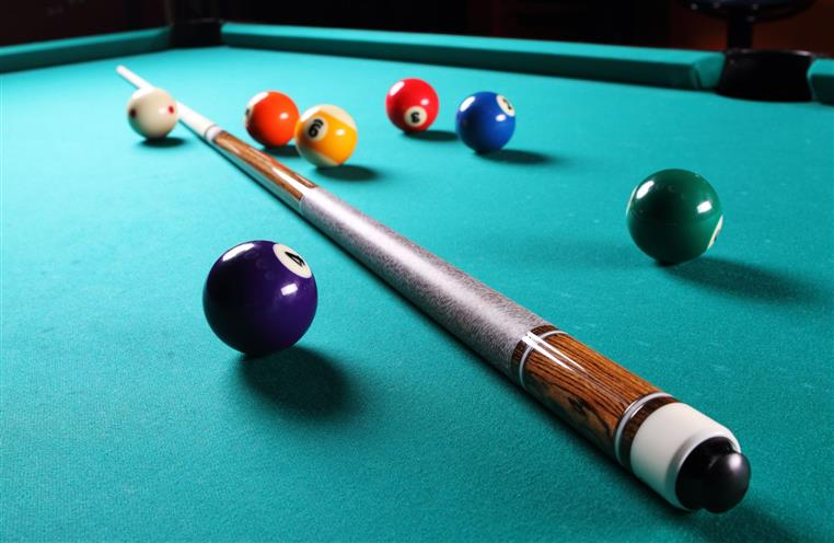 billiards table with a pool cue and balls