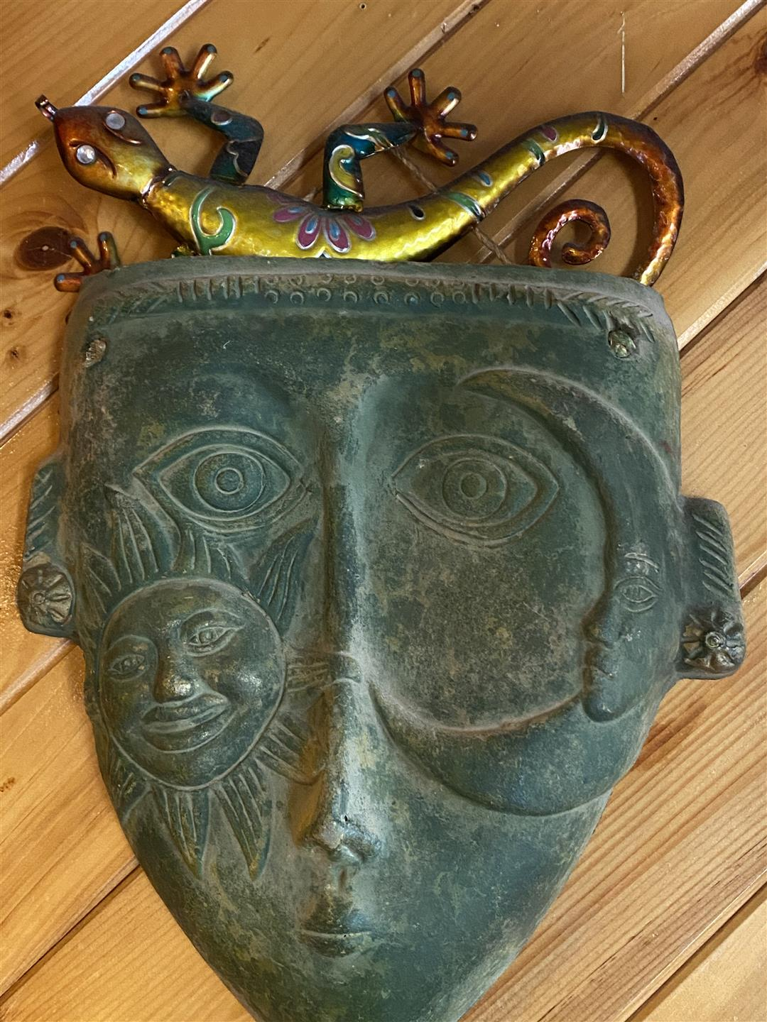tribal mask and metal lizard decoration hanging on wall