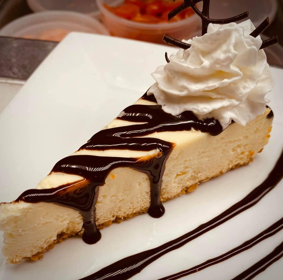 cheesecake topped with chocolate sauce and whipped cream