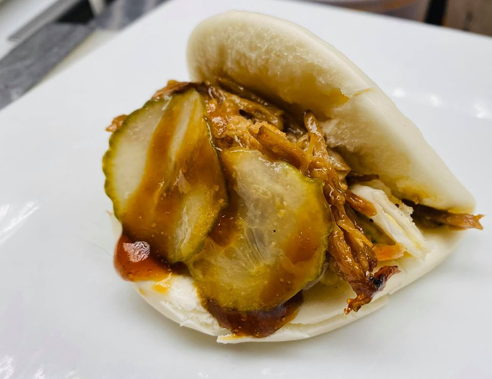 Pork Bao Buns filled with shredded pork, slaw, soy glaze, and homemade pickles
