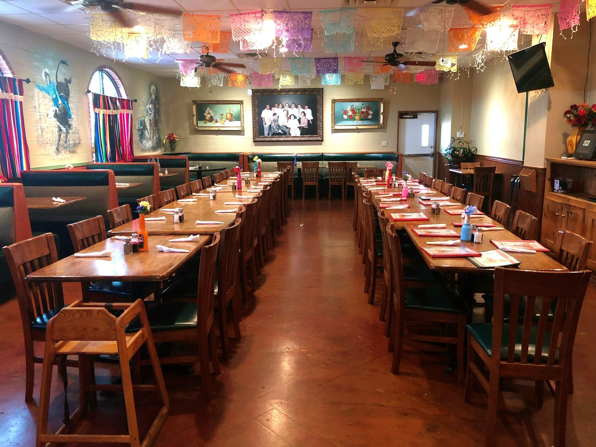 table set up in the private room with mexican decorations hanging from the ceiling