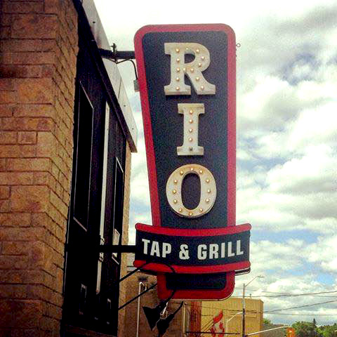 "The sign outside of the restaurant that says ""Rio, Tap & Grill"""
