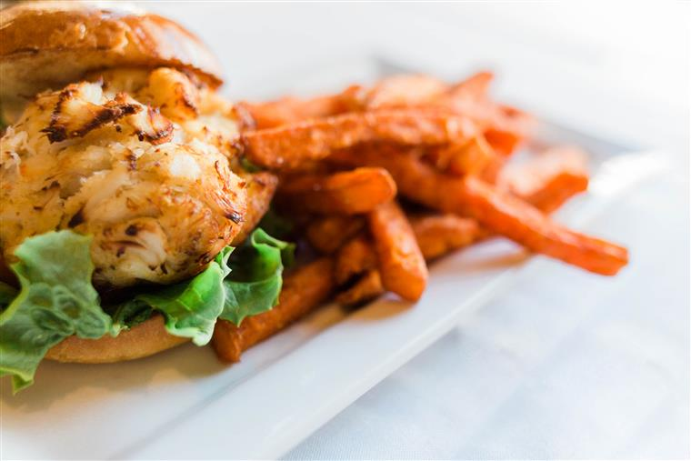 grilled chicken sandwich on a brioche bun with lettuce, side of sweet potato fries