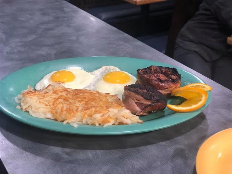 two eggs sunny-side up with hashbrowns and meat on the side.
