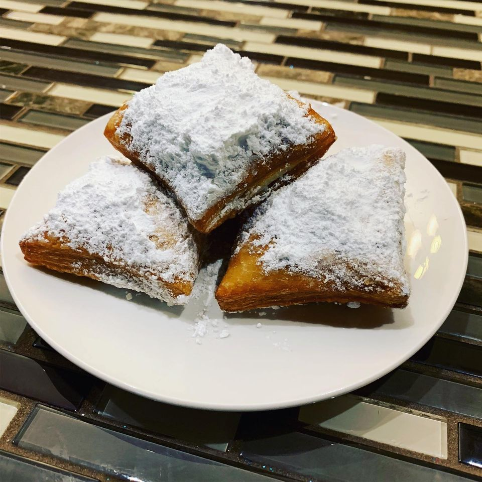 plate of beignets with powdered sugar