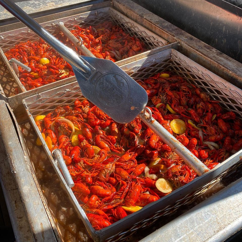 containters of crawfish with lemons and a spatula