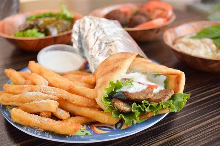gyro and fries on plate with various grill items