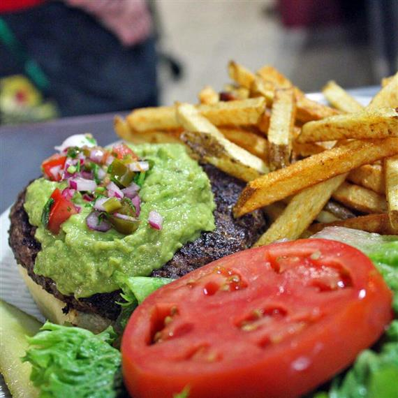 A burger topped with guacamole, diced onion, lettuce, and tomato with a side of French fries