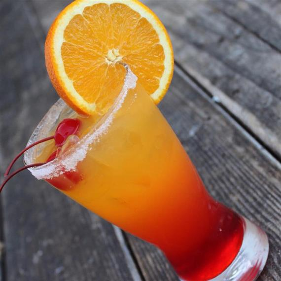 A cocktail topped with an orange slice, cherries, and a sugar rim