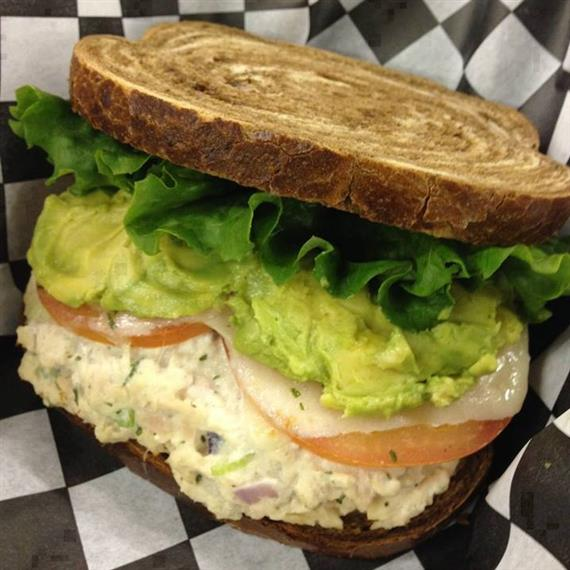 chicken salad sandwich with lettuce, tomato, cheese, and avocado on marble rye bread