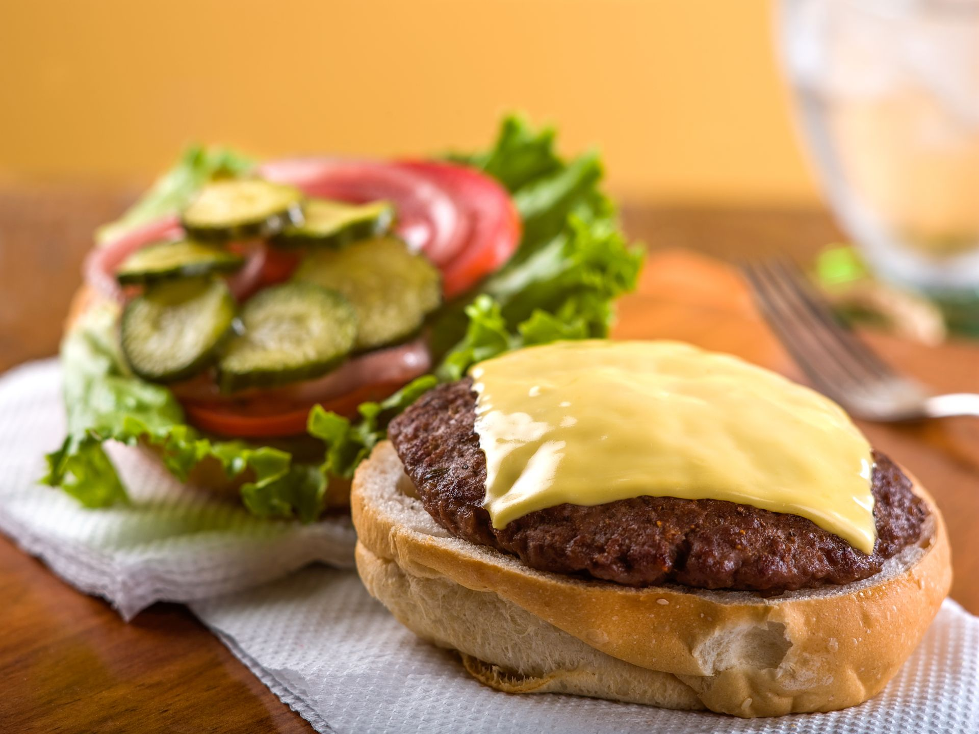 cheeseburger with lettuce, tomato, onions and pickle slices