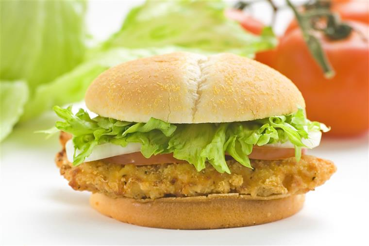 A chicken sandwich with lettuce, and tomato on a bun