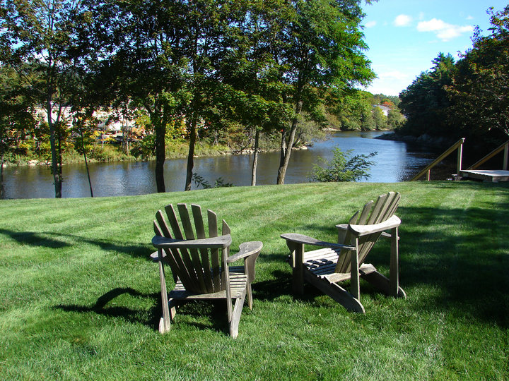 two adirondak chairs overlooking the shore of the Union River