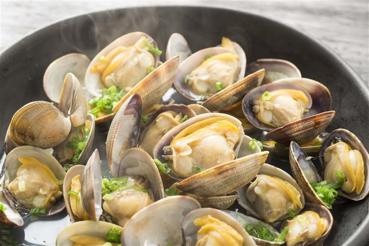clams being steamed in a pot with green garnishes