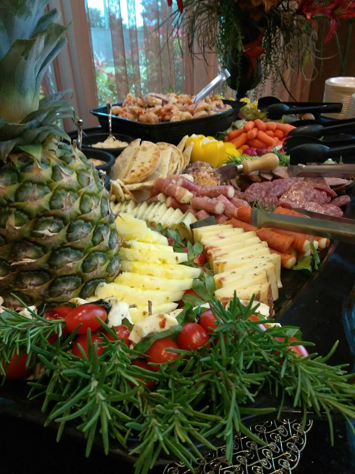 table of cold appetizers including assorted fruit, meats, cheese, and veggies