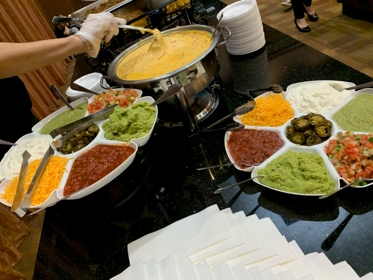 nacho station at an event with nacho cheese, guacamole, salsa, shredded cheese, jalapenos, and sour cream