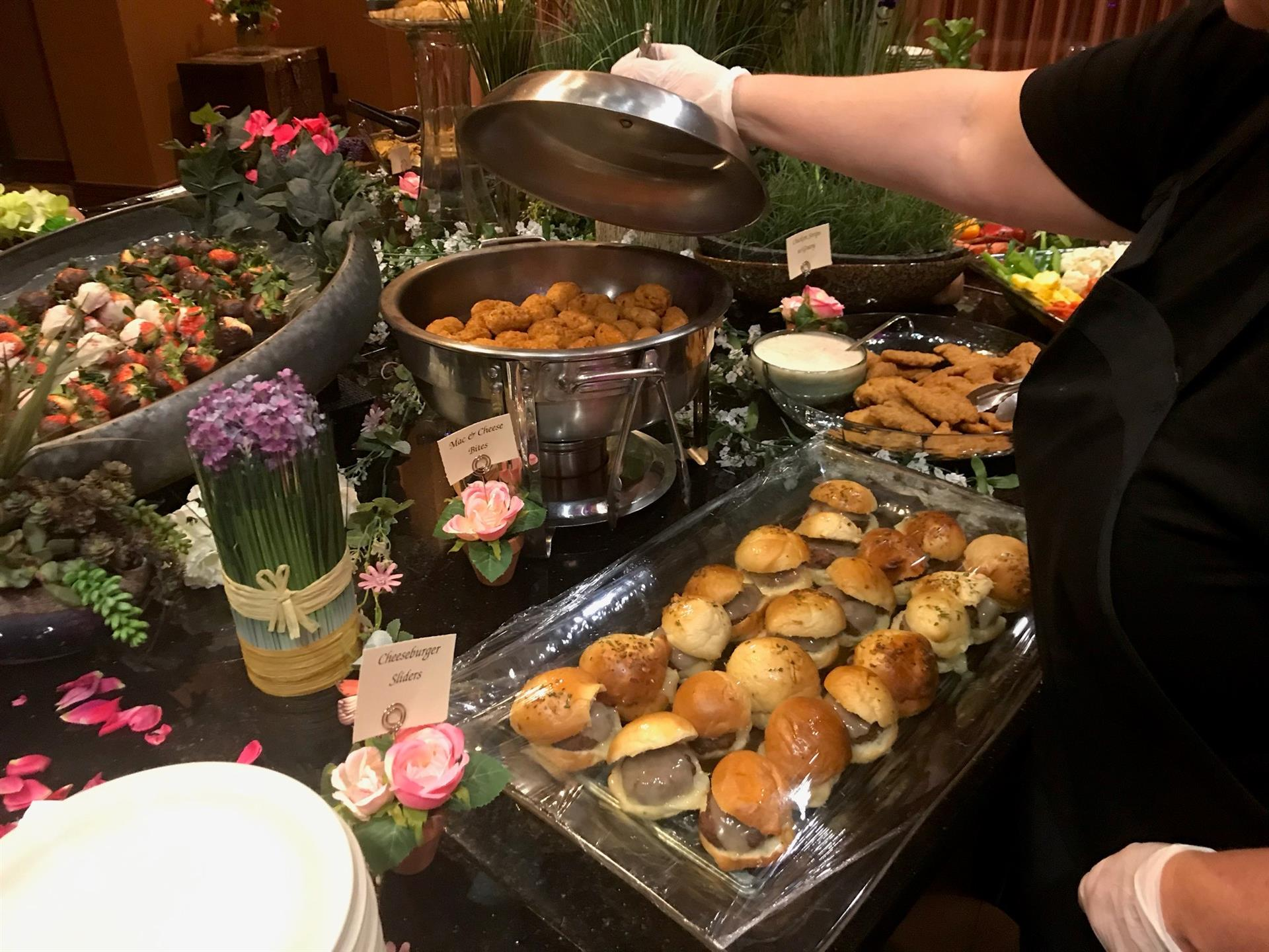 table of hot foods at an event including hamburger sliders and mac and cheese bites