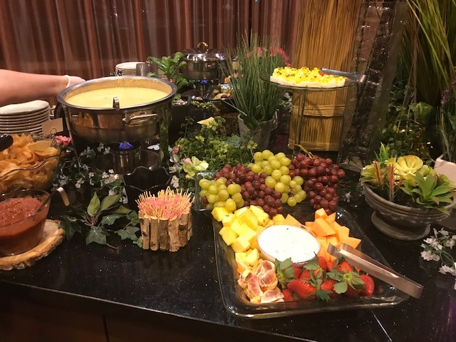 table with a bowl of soup and a platter of grapes and cheese