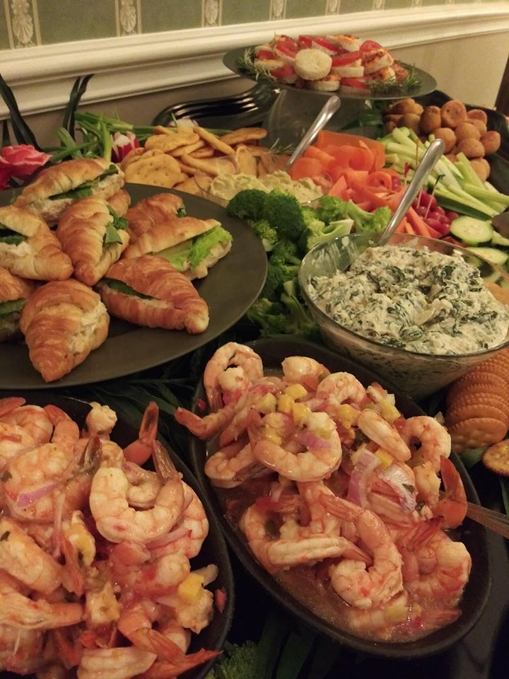 platters of shrimp, sandwiches, and vegetables with dip