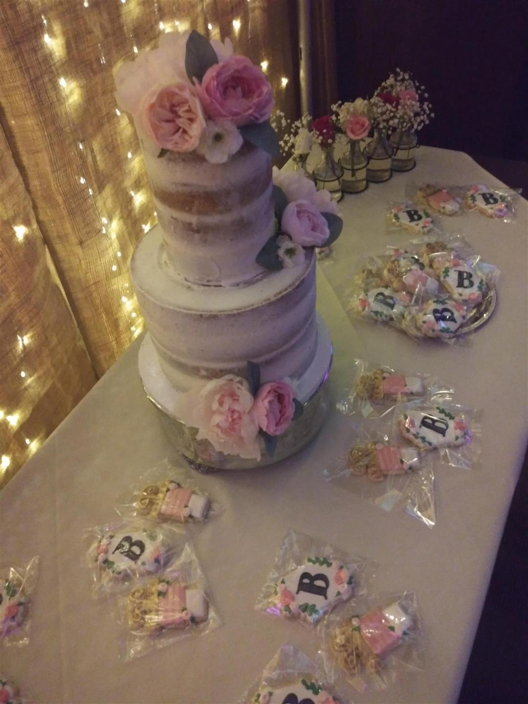 "table with wedding cake with roses and cookies with a ""B"" written on them"
