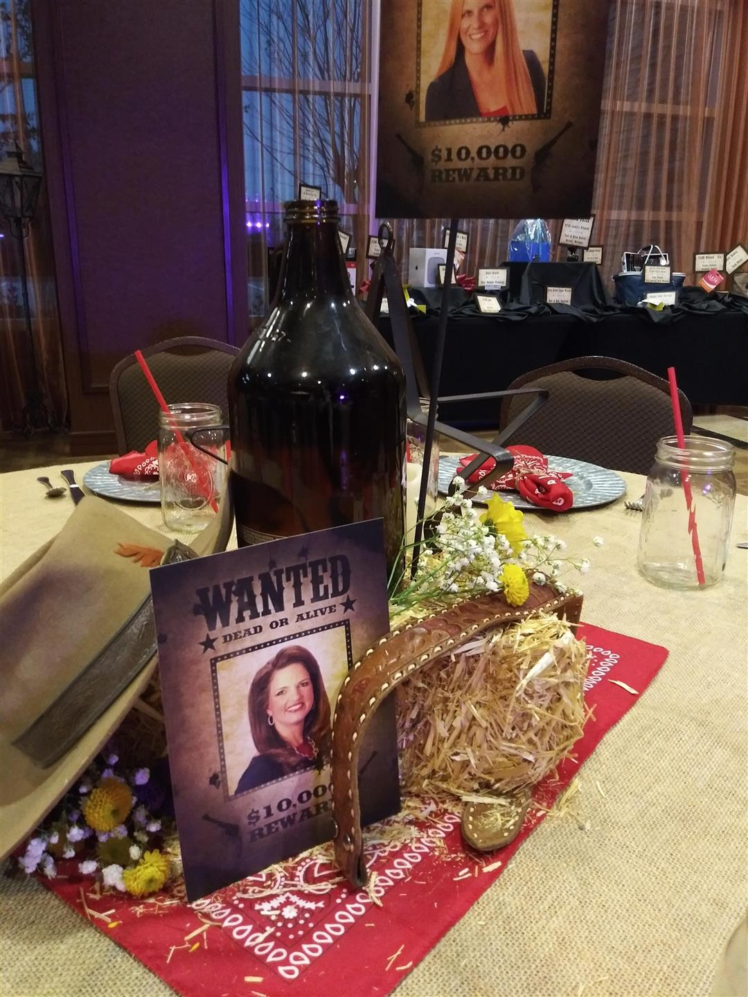 table centerpiece for cowboy party including wanted poster, hay bale, a bandana, and a beer growler