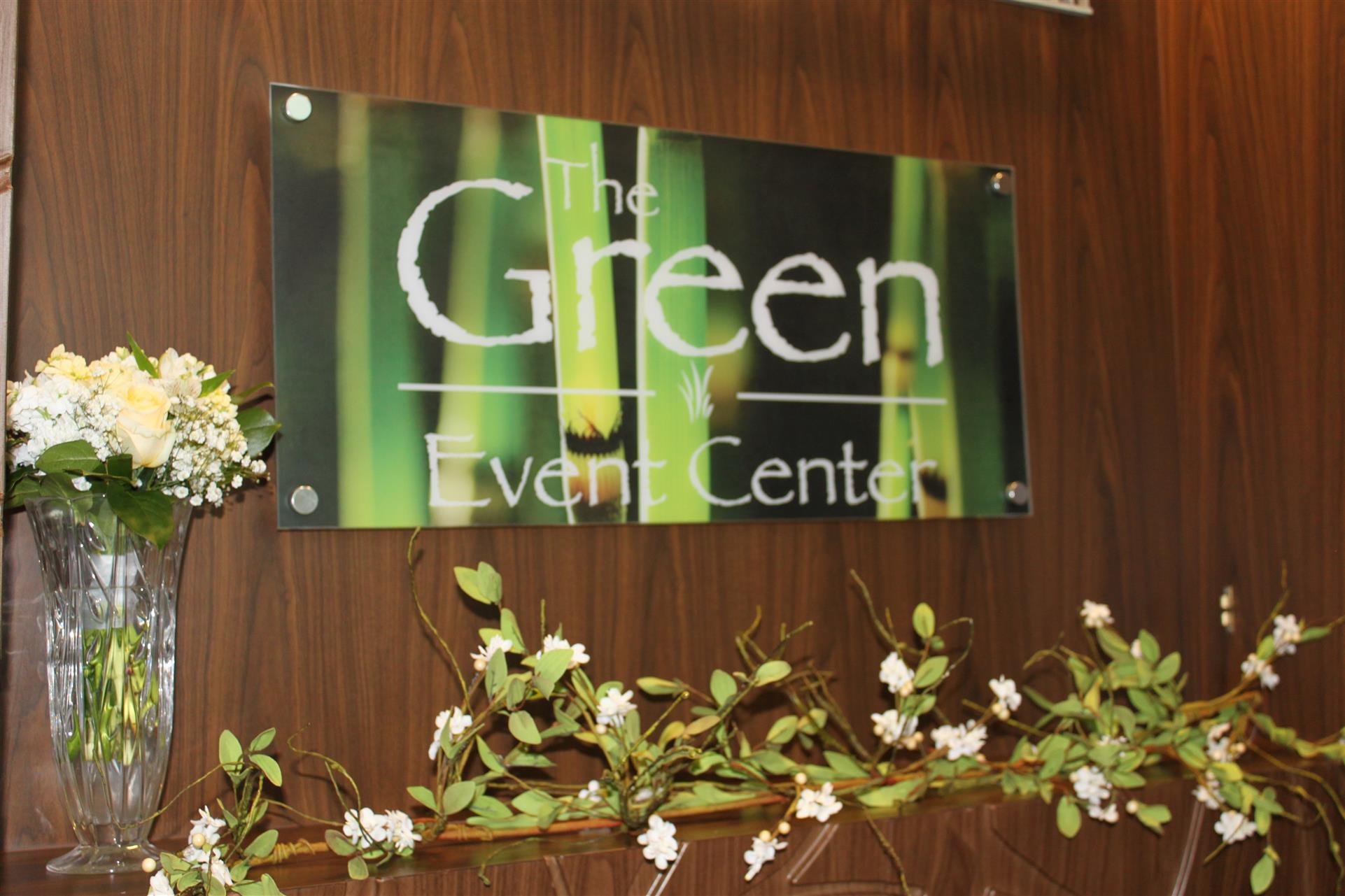 """sign reading """"The Green Event Center"""" with flowers underneath"""